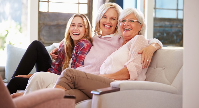 Mother, daughter and granddaughter sat on a sofa smiling