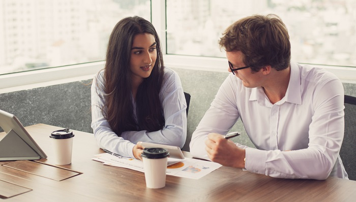 An  image of a man and a woman having a discussion over coffee whilst seated at a desk