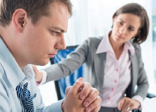 Man being comforted by woman at work
