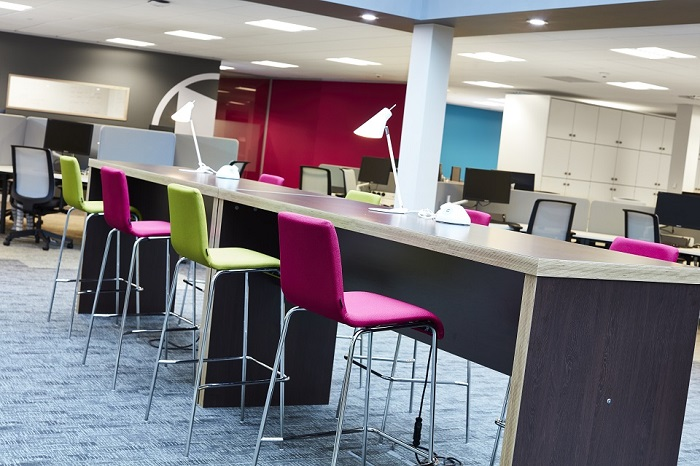 A row of multi-coloured hot desks and high chairs