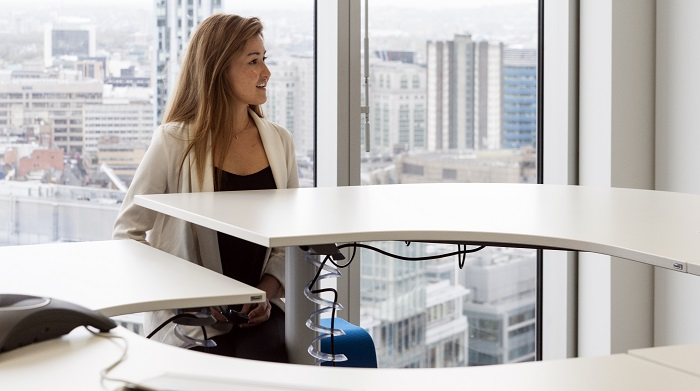 Woman sitting at a sit/stand desk