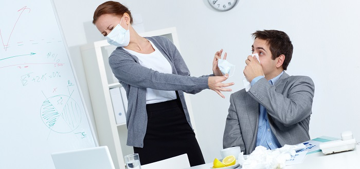 Woman wearing a surgical mask handing a man with a cold a tissue