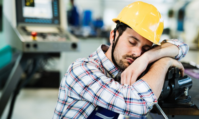 Male worker wearing hard hat and sleeping against machinery