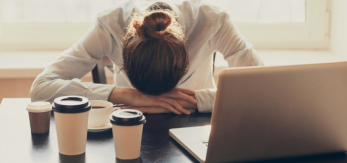 Woman asleep at her desk surrounded by coffee