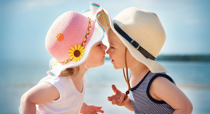 Baby boy and girl face to face wearing hats on the beach