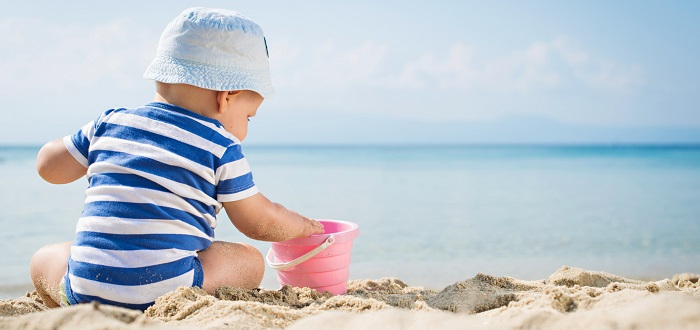 Baby playing in the sand with a bucket on the beach