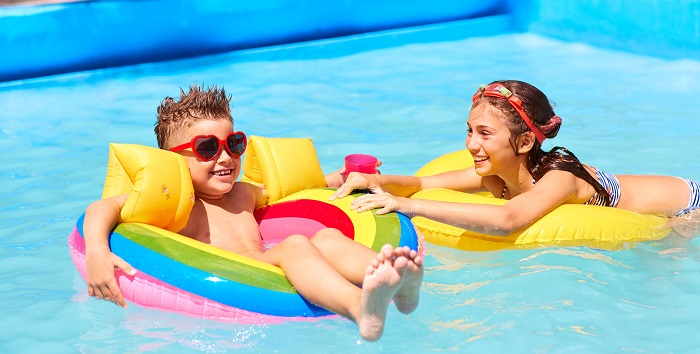 Boy and girl playing in a swimming pool on inflatables