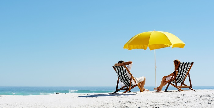 An image of a couple on a beach, sitting in deck chairs with a sun umbrella.