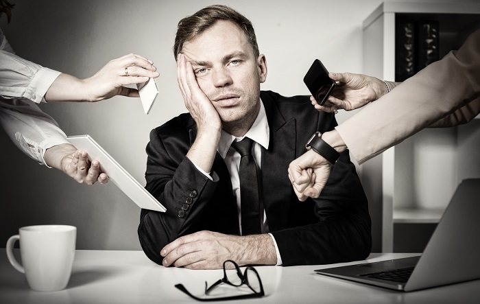 stressed man at work with too much to do