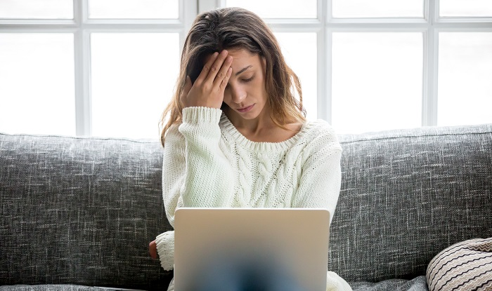 Stressed woman at laptop on sofa